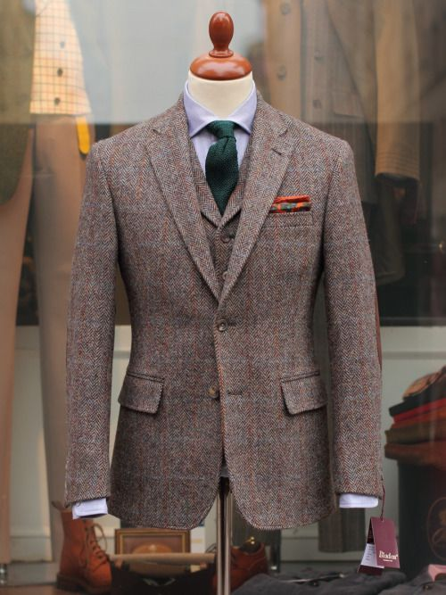 Light brown (with red) tweed suit, light blue shirt, green tie