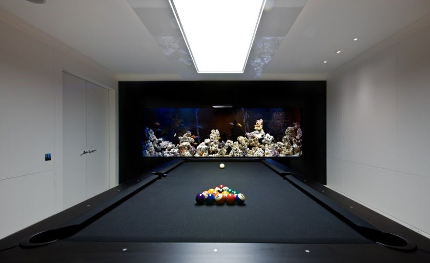 Black pool table with light panel above large fish tank for Fish tank built into wall