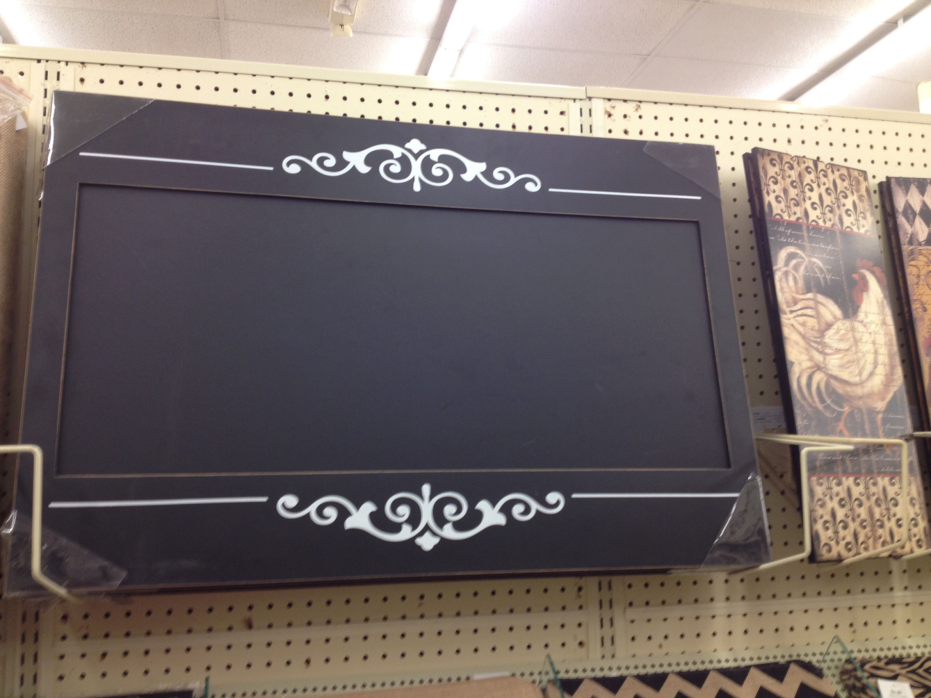 Chalkboard paint with a raised thick frame and painted white design.