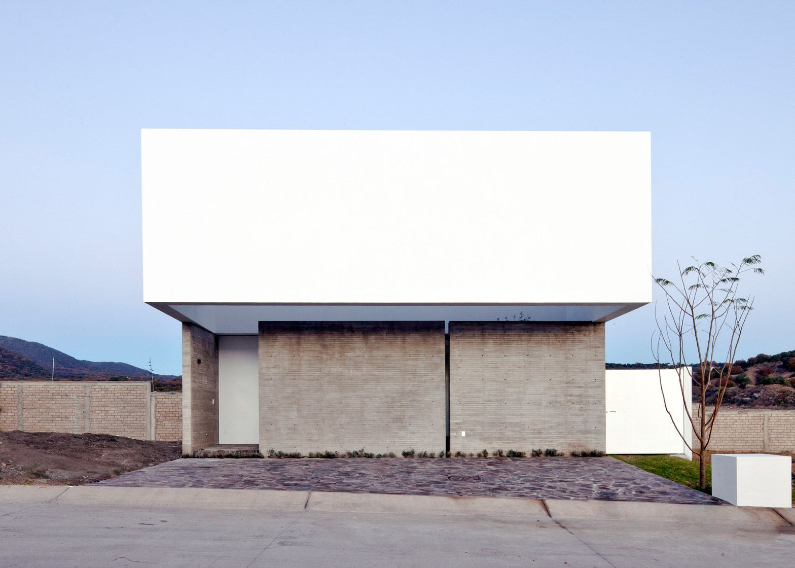 A white-rendered concrete screen extends from this house in Mexico ...