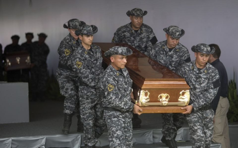 Officers carry victims of a recent battle with members of