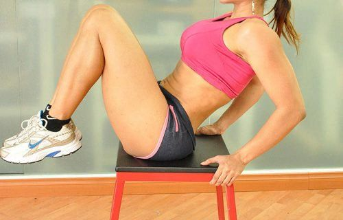 Übungen mit Stuhl für einen flachen Bauch: Anheben der Knie zur Brust