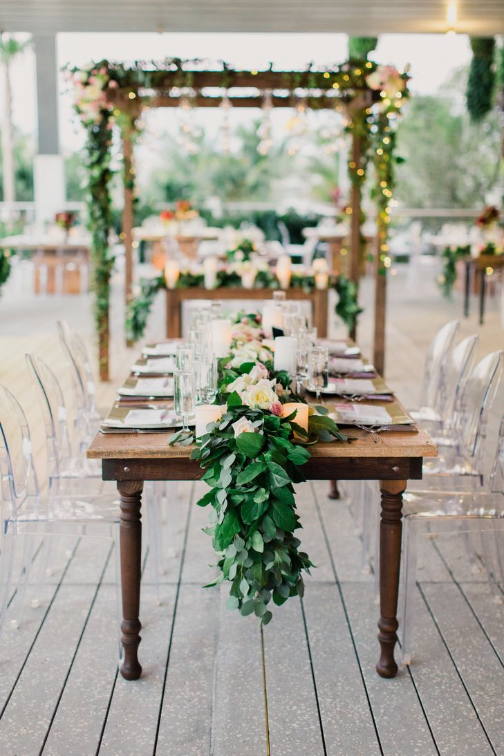 Raw, wooden family-style table for garden themed wedding reception ...