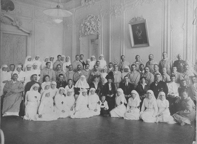A Imperatriz Viúva Maria Feodorovna, Grã-duquesa Xênia Alexandrovna da Rússia que estava acompanhada por seus dois filhos mais novos de roupa de marinheiro, Princesa Irina Alexandrovna Yussupova e seu marido Felix Yussupov entre funcionários do Hospital e feridos.