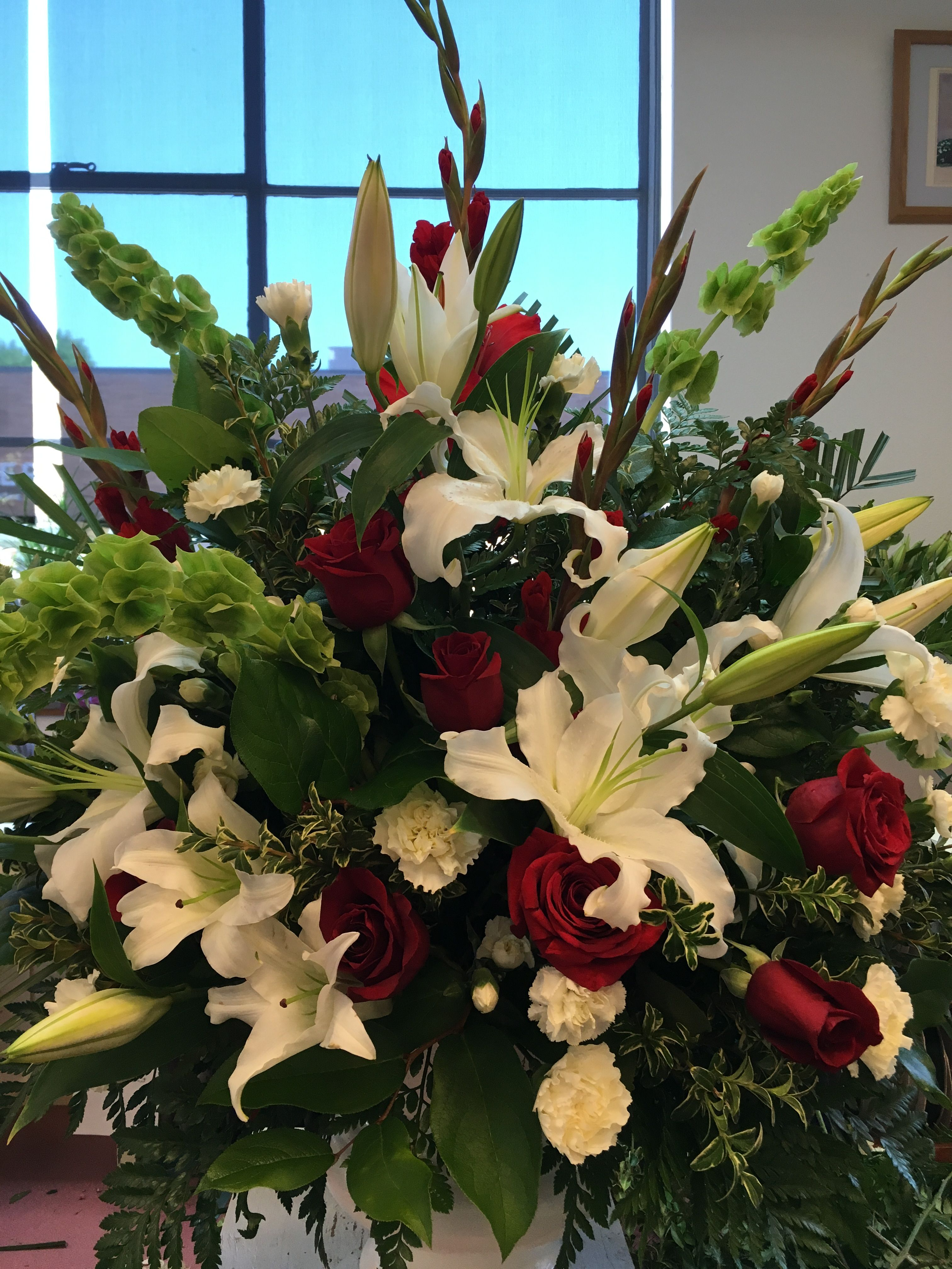 Lovely urn arrangement for a funeral includes bells of ireland red lovely urn arrangement for a funeral includes bells of ireland red roses white oriental izmirmasajfo
