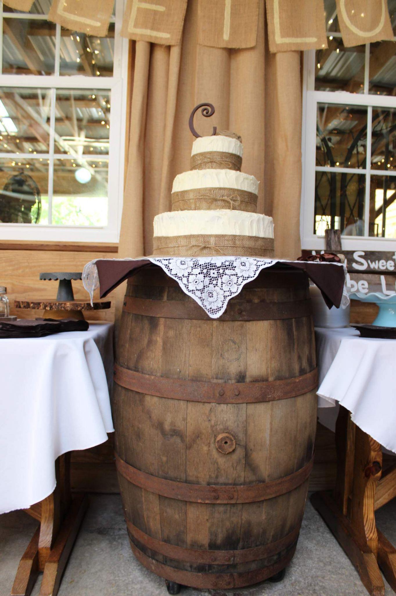 Wedding cake with burlap ribbon trim and whiskey barrel