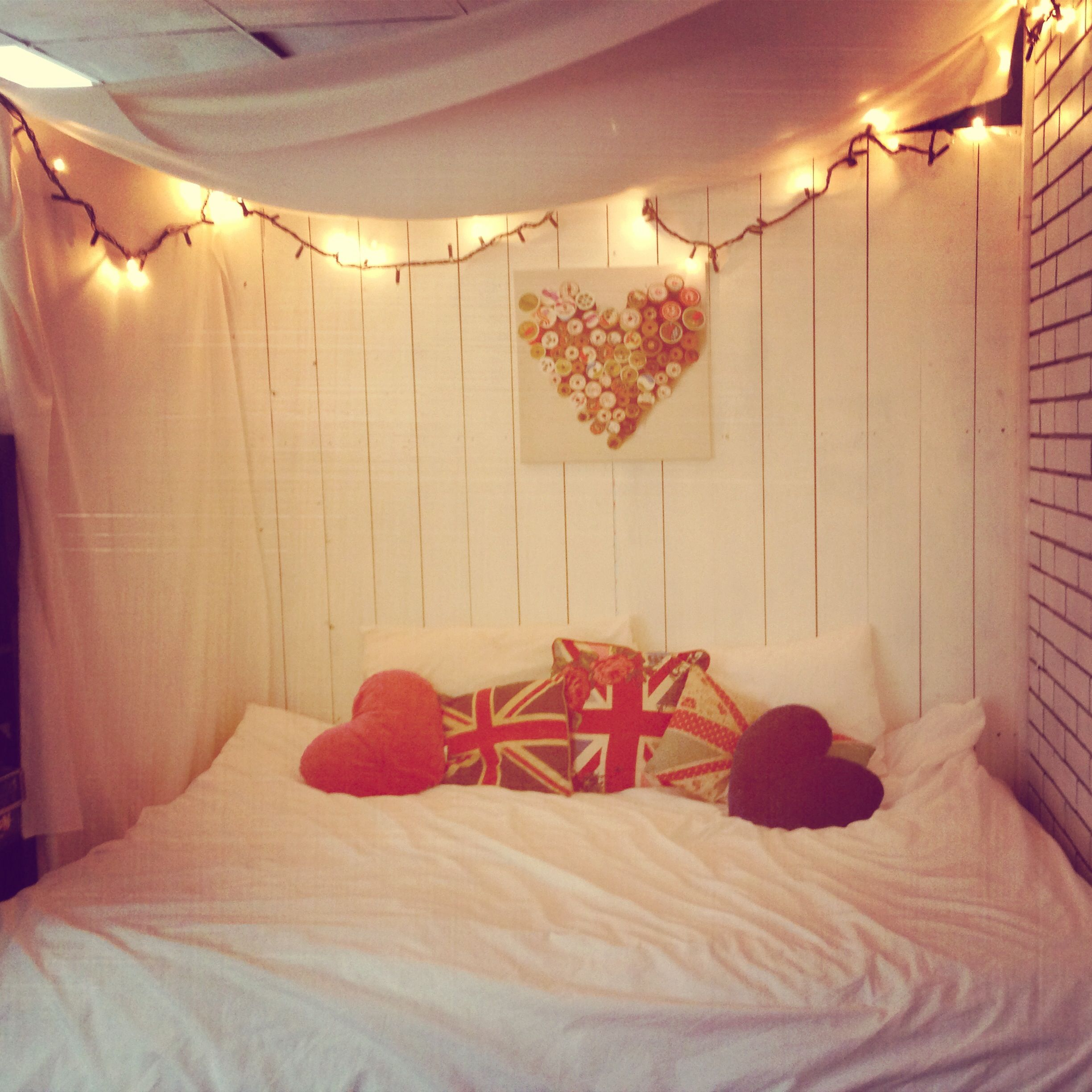 Cosy canopy bed using white satin and fairy lights. Simple ...