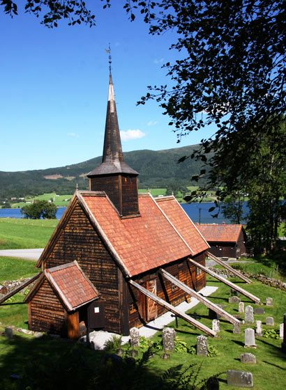 Rødven stave church looking over Rødvenfjord. - Romsdal. This is an one-nave stave church, whose oldest components originate from the end of the 1100's. It has been considerably altered during the course of time. A crucifix dating to the middle 1200's belongs to the old interior.