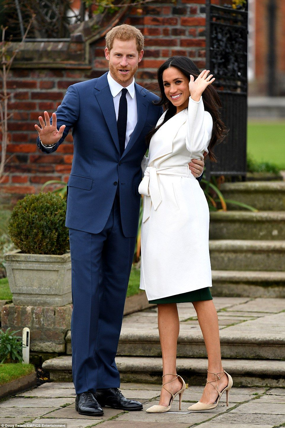 Meghan looked resplendent in a chic belted white coat dress and vertiginous heels as she c...