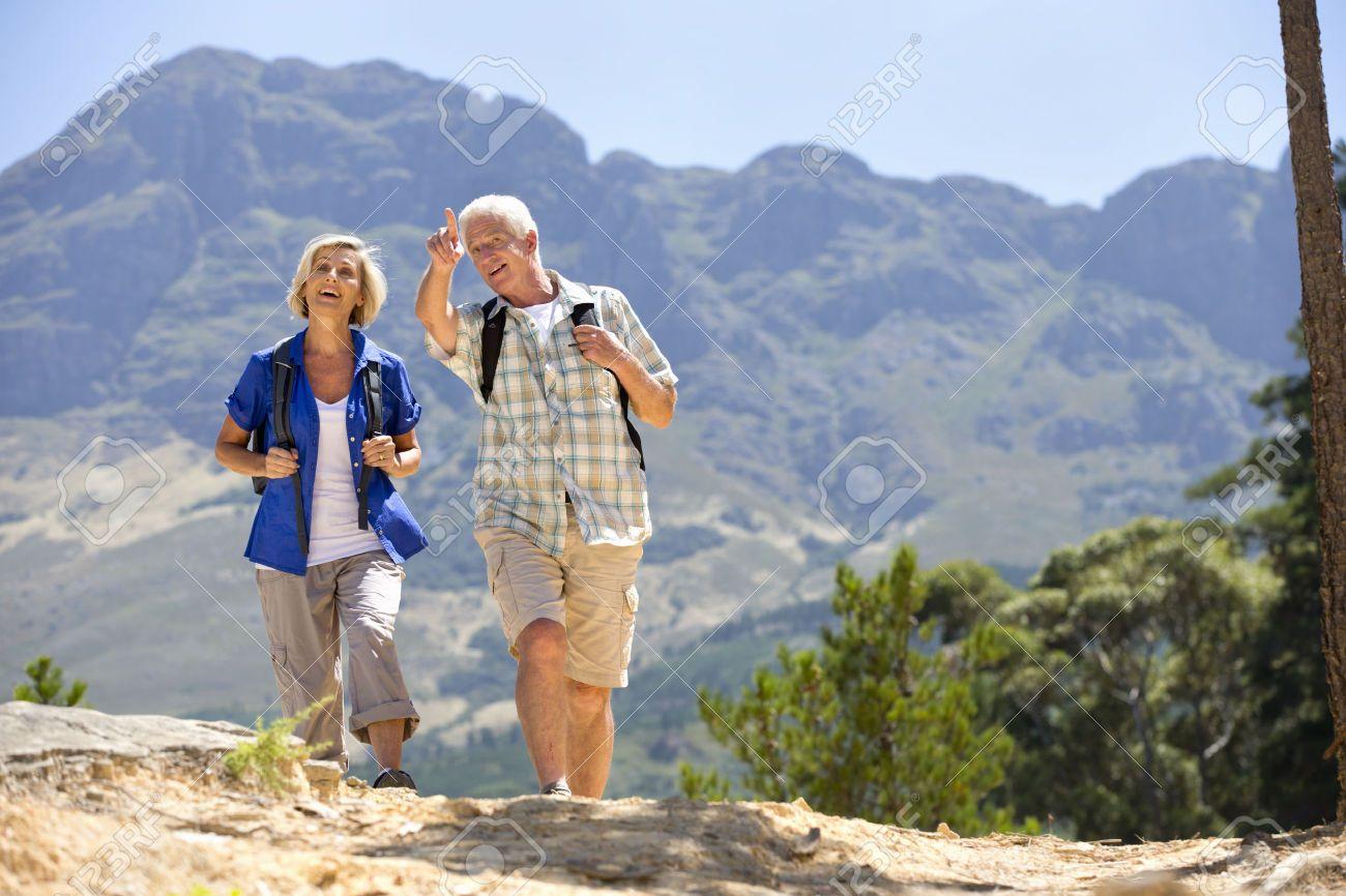 Walking Together Older Couple Hiking On Rural Hillside Couples