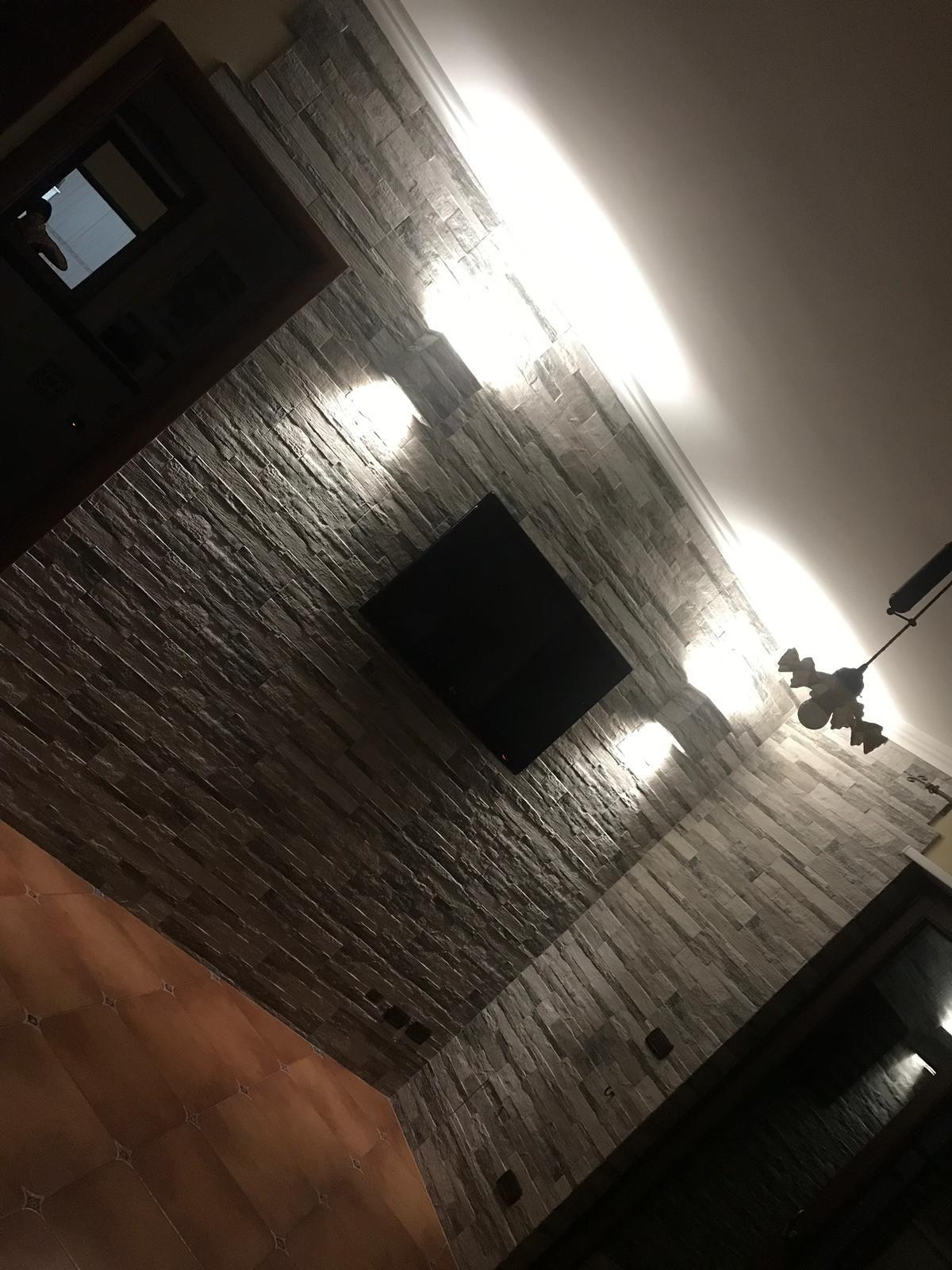 Parete soggiorno con rivestimento effetto pietra e lampade ...