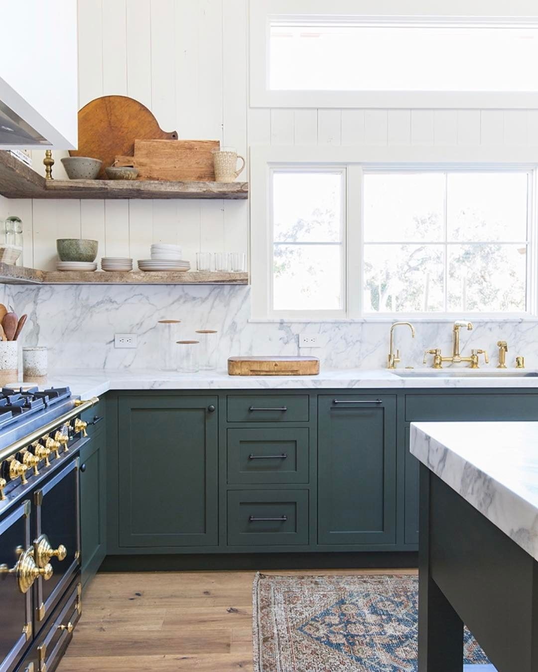 green kitchen cabinets, black and brass stove and open shelving ...