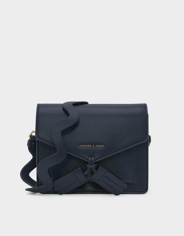 b2ec94c162 Navy front flap bag featuring tassel details and a magnetic closure. Comes  with a long