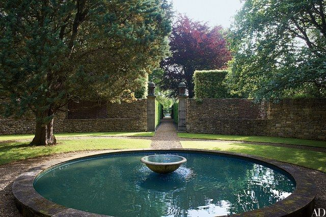On the grounds of decorator Anouska Hempel's English residence, a garden fountain is encircled by Cotswold drystone walls.