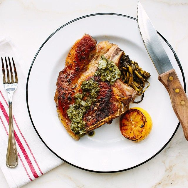 A perfectly-cooked pork chop, braised chard, home-made salsa verde, grilled lemon.