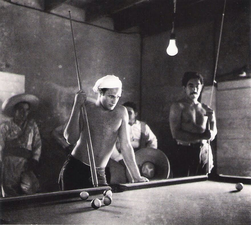 Marlon Brando, Anthony Quinn in background. Taking a break from the shooting of Viva Zapata, 1952. (Sam Shaw)