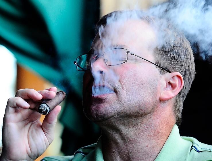 Mike Waight, who has been coming to the Midwest Cigar Summit for five years, exhales smoke from his cigar Friday while taking part in the annual event sponsored by the Gentleman's Cigar Society of Peoria.