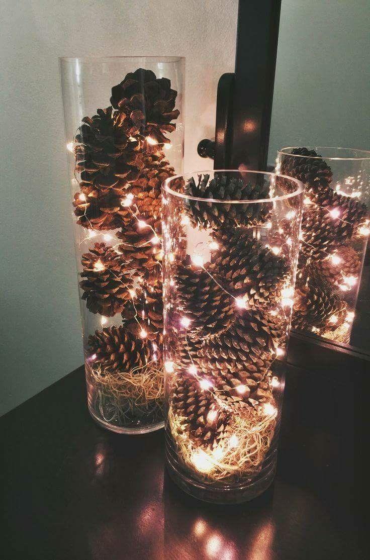 Funkelnlichter und Kiefernzapfen, die in einer klaren Vase eingebettet sind, machen einen schönen, rustikalen Wein
