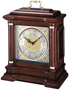 """The Seiko QXJ004BLH-X Oak Carriage Mantel Clock is a Large Carriage Style Clock with Seiko Quality Dark brown solid oak case with hand rubbed finish. Glass crystal. Ornate metal dial features intricate vine pattern. Applied numerals. Brass handle. Westminster/Whittington quarter-hour chime, hourly strikes. Volume control. Nighttime chime silencer. One C battery included. Size: 16 1/4"""" x 11 3/4"""" x 6 3/4"""""""