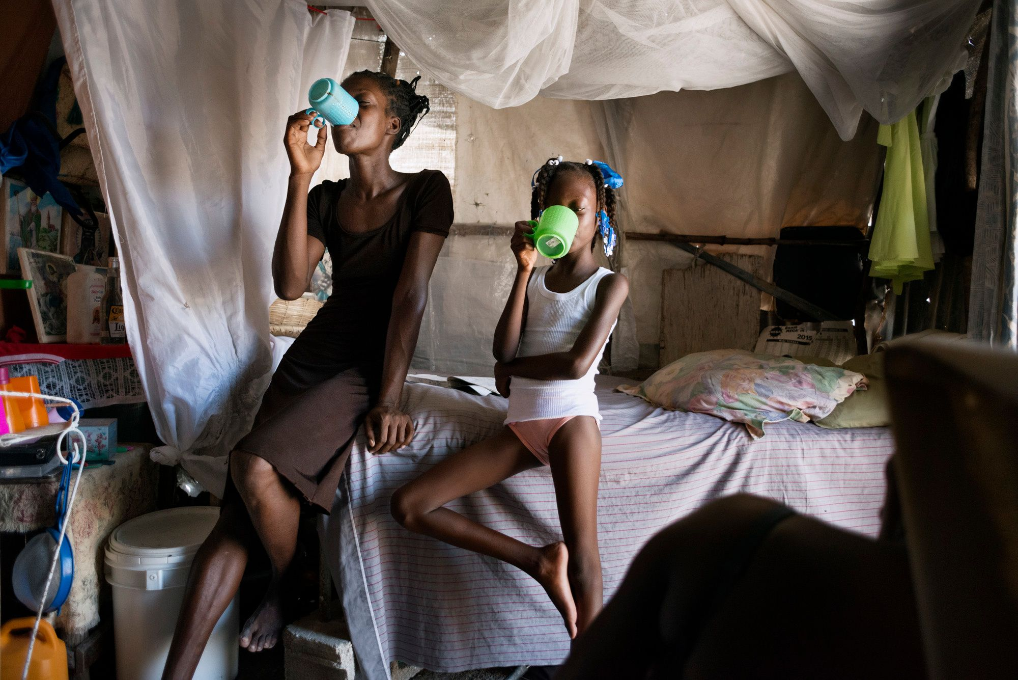 Nadie, 28, together with her daughter, 10. They are both drinking non-potable water in the shelter where they live. Nadie emigrated with her husband and daughter from St. Michel de Latalaille in the province of Cap Haitien to Port au Prince in 2010. They used to cultivate rice and vegetables and then sell them in the market but the production has dropped in recent years to the point that the farm could not support them. They sold their house and their land for a tiny amount of money and…