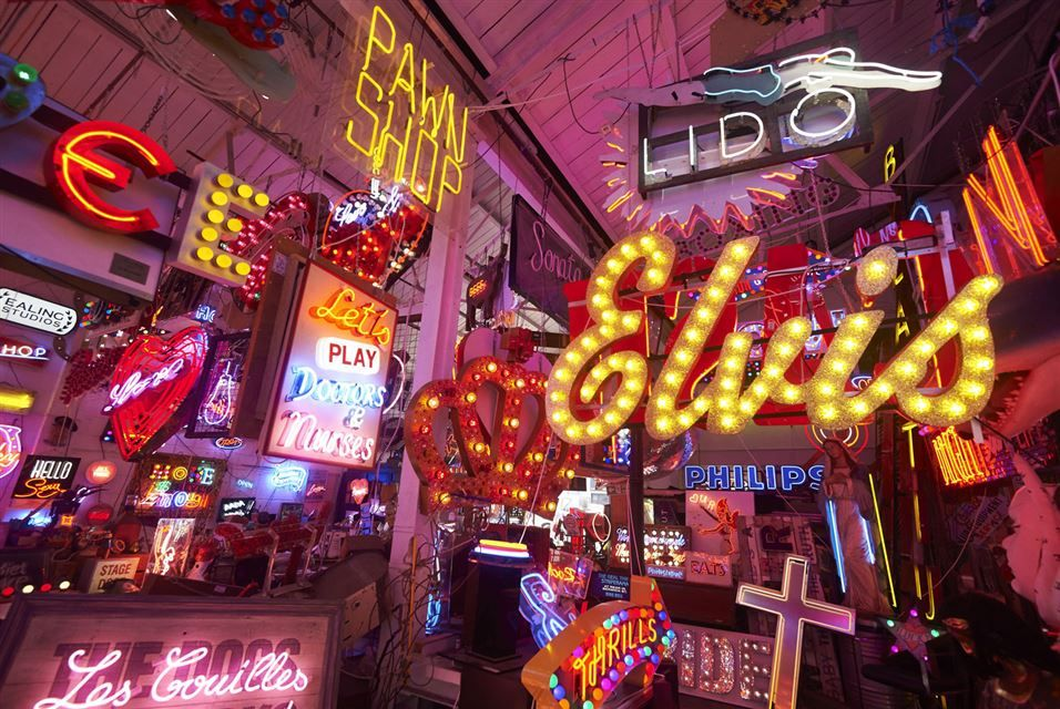 An array of neon lights and signs are displayed inside god