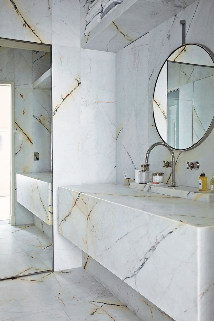 Floor to ceiling marble bathroom, Joseph Dirand's Paris apartment, simple lines, white marble, strong amber + grey veining in marble