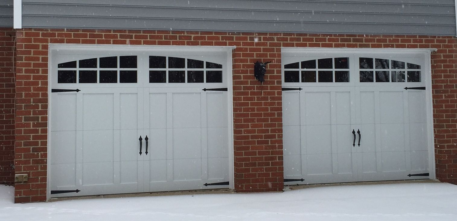 two 9x7 model 5632a carriage style overlay garage doors with arched stockton top glass installed by