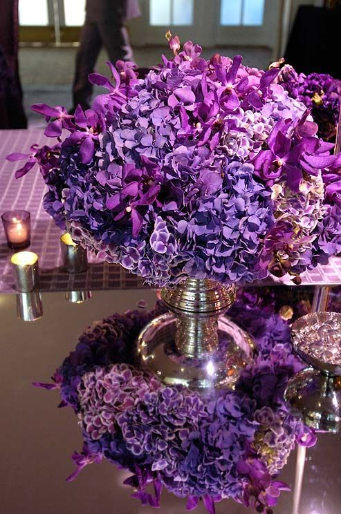 An overflowing arrangement of purple hydrangeas and orchids reflect off the mirrored tabletop.