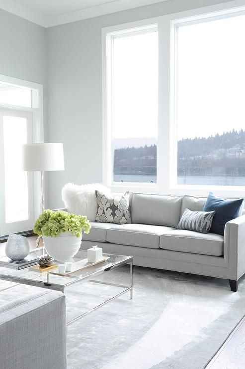 Calming Light Gray Walls Frame Large White Frame Windows In This Well  Designed Living Room With A Water View.
