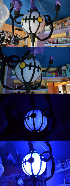 """Chandelure lamp (originally made be Drak-Gimla-Hongki) Made with wire, rice paper, and crepe paper. Black cloth is used to cover the """"leg""""; the flames are painted purple cotton (though I'd probably change it to something else to prevent a fire hazard). A blue LED bulb gives the lamp its etherial glow. This looks like a fun craft project to take on this summer..."""
