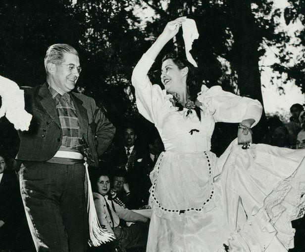 Esta fotografía muestra una pareja en trajestradicionales y bailando la zamba, una de lasformas de danza más populares de Argentina. La danza se originó en el Perú en el género criollo conocido como el zamacueca, que fue adoptado en Chile como la cueca. La zamba es un baile lento en tres cuartos de tiempo que suena principalmente en guitarra y en bombo legüero (el bombo de los pueblos indígenas argentinos). La fotografía pertenece a la colección de la Biblioteca Conmemorativa de Colón de…
