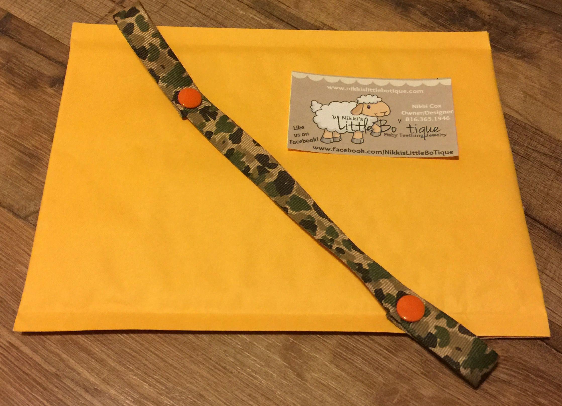 Camo binki/teether holder with orange snaps will be on it's way to California tomorrow!!  www.nikkislittlebotique.com