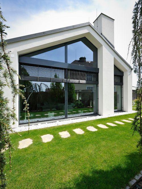 Cette image montre une façade de maison design de plain-pied ...