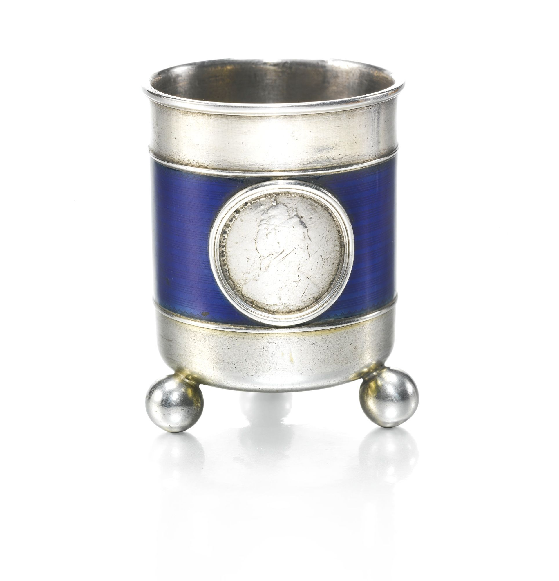 AFabergé silver and enamel vodka beaker, workmaster Anders Nevalainen, St Petersburg, 1899-1904   Lot   Sotheby's -cylindrical, the side enamelled in a band of translucent midnight blue over engine-turned stripes, the front inset with a silver ten kopek coin of Empress Catherine II dated 1784, on three ball feet, struck with workmaster's initials and K. Fabergé in Cyrillic, 88 standard, scratched inventory number 10016 height 4.7cm, 1 7/8 in.