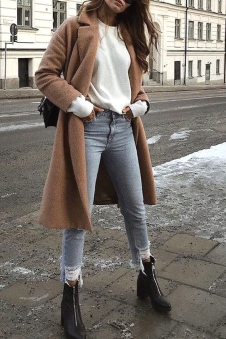Trendy fall / winter women's fashion with a long camel coat, destroyed jeans, a white sweater and ankle boots