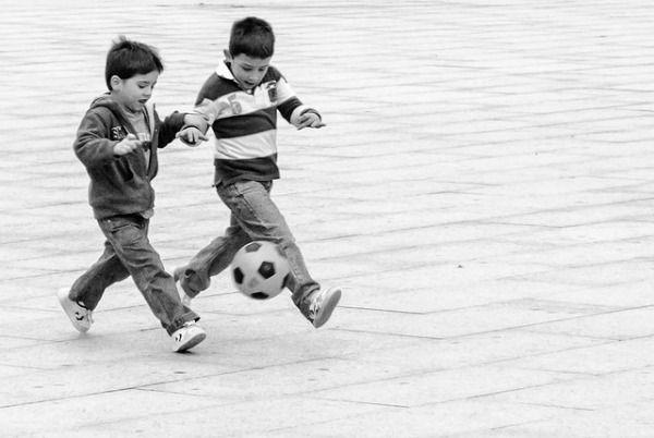 Foto de dos chicos corriendo detrás de un balón