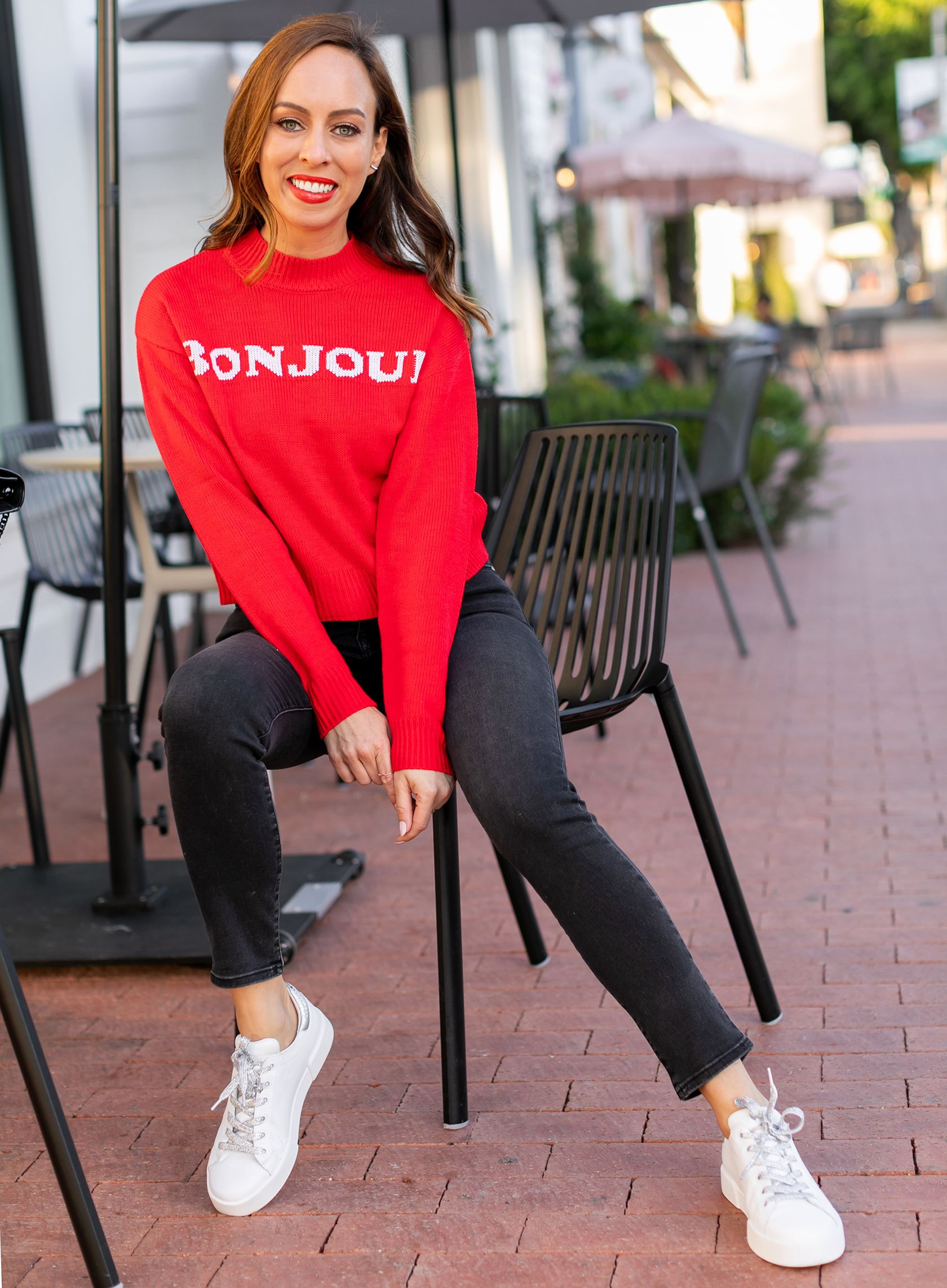 6653d9aee4 Sydne Style shows casual outfit ideas in red graphic sweater and white  sneakers