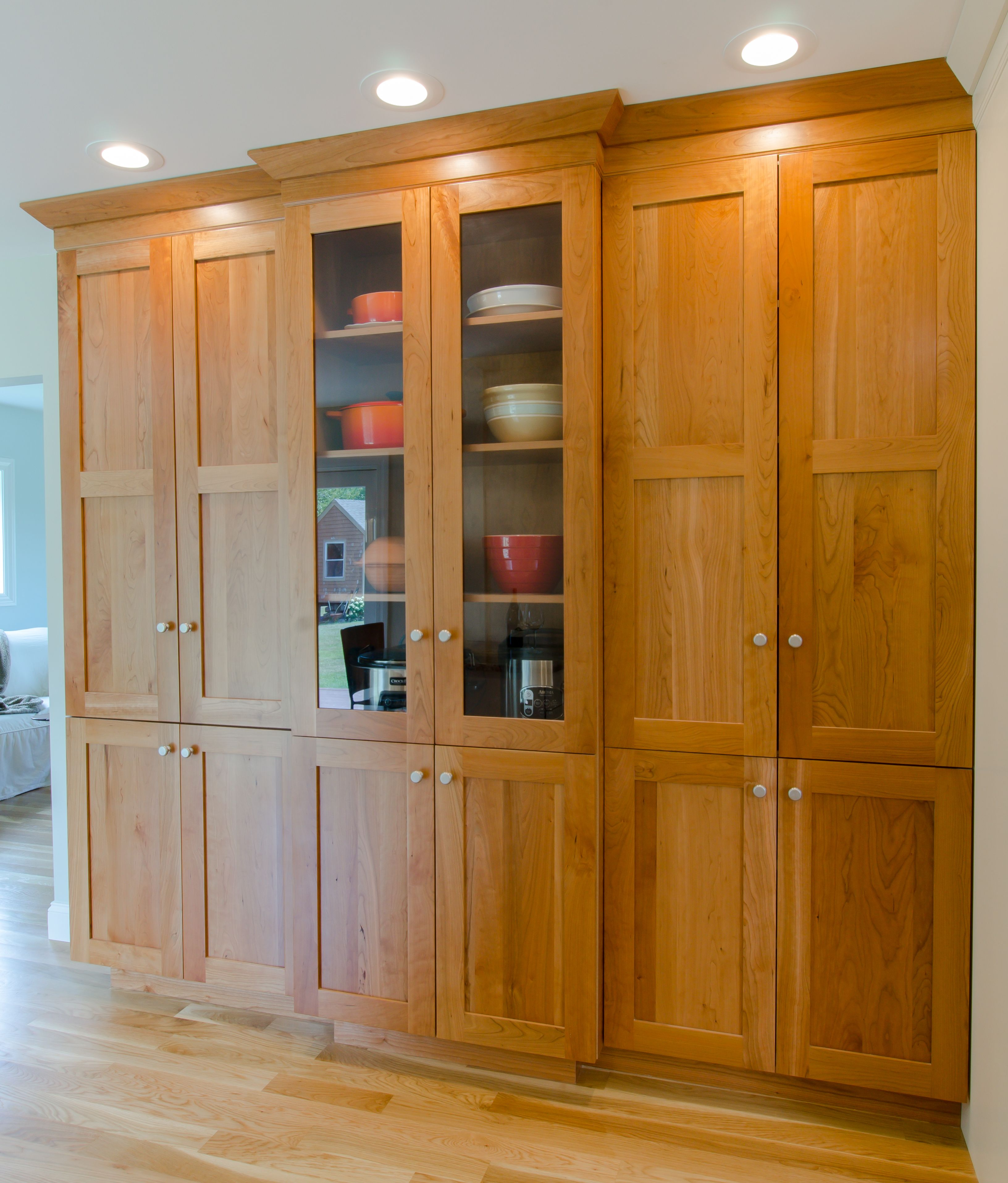 Kitchen pantry large pantry cabinet in natural cherry with glass cabinets in the middle