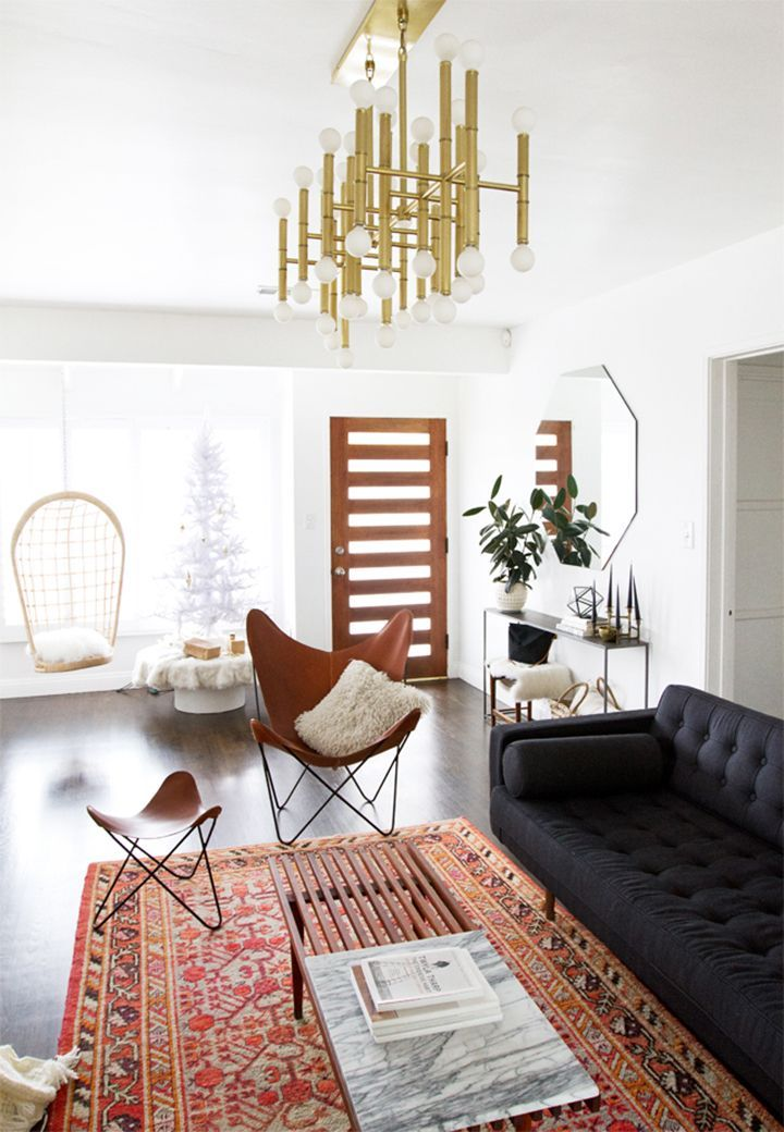 A mid-century modern living room with a dark sofa and brass lighting