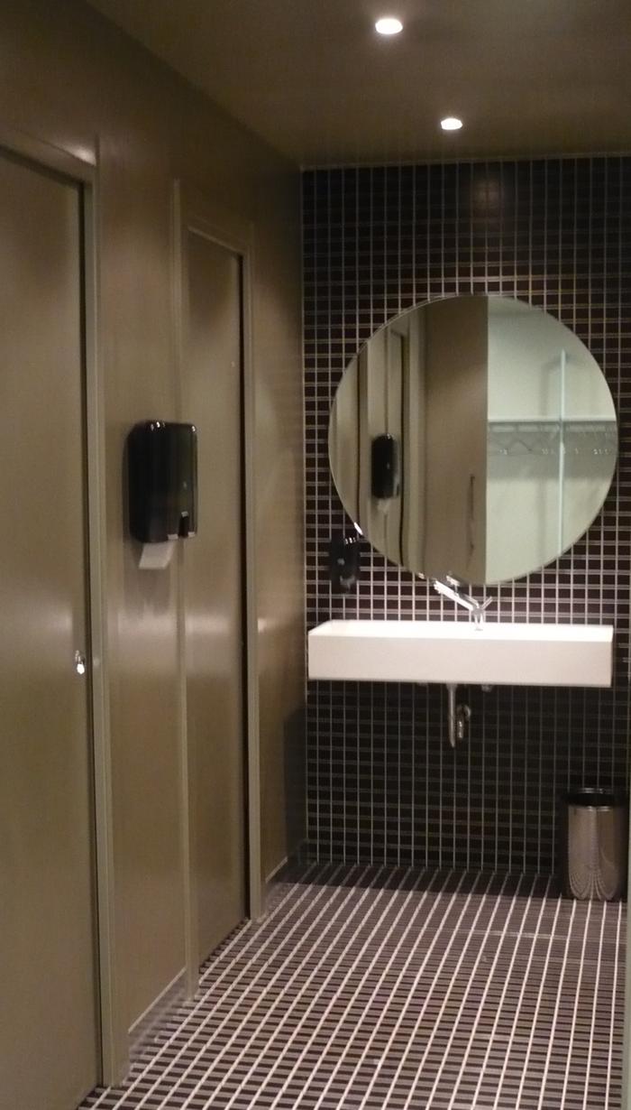 Baño de oficina con un pre-corte negro tanto en suelo como en paredes y pintura de color oro en puertas y techo.