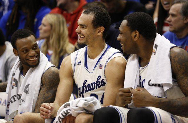 Kansas forward Perry Ellis, center, smiles as he is congratulated by his teammates Naadir Tharpe, left, and Tarik Black after leaving the game following a 32-point effort against TCU on Saturday, Feb. 15, 2014 at Allen Fieldhouse. #KU