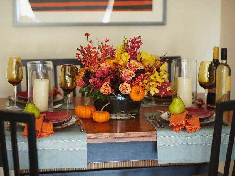 centre de table original composé de roses, baies rouges, mini citrouilles et feuilles