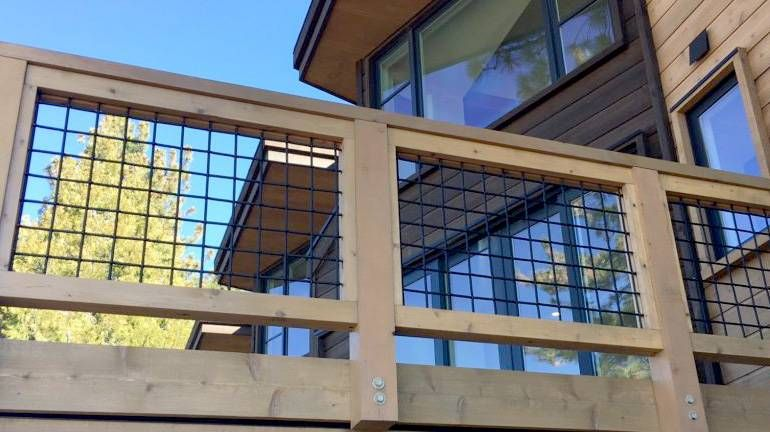Black Wild Hog Panel Railing Installed Between Cedar Deck Rails At