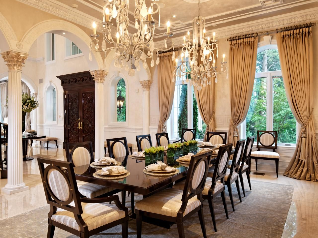 A Stunning Wood Dining Table With Seating For Eight Draws You Into This Formal Room French Pleat Drapes Double Chandeliers And Decorative Arches