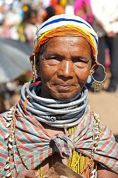 Smiling Bonda tribeswoman wearing cotton shawl over traditional bead costume, beaded cap, large earrings and metal necklaces, Rayagader, Orissa, India, Asia ...