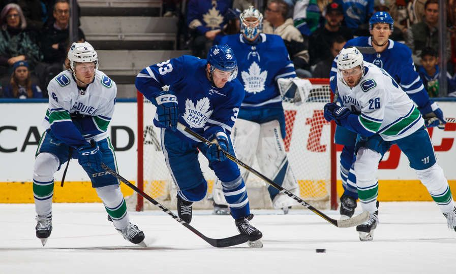 a25d5e19247 Frederik Gauthier  33 of the Toronto Maple Leafs skates between Brock  Boeser  6 and Thomas Vanek  26 of the Vancouver Canucks during the first  period at the ...