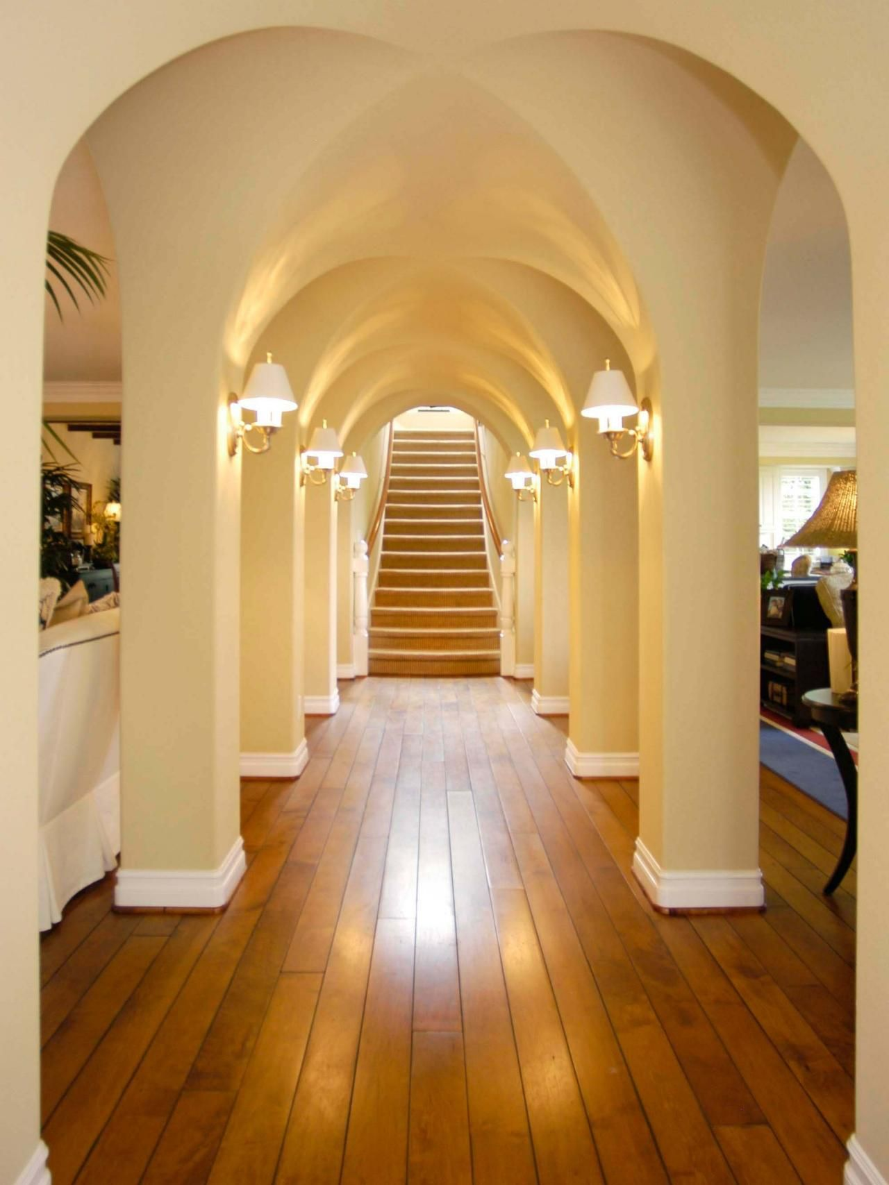 Sculpted archways lead to a staircase in this elegant ...