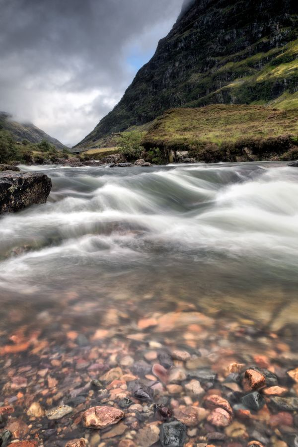 by Chris Frost - A stream tumbles down the mountainous hillside across rustic rock in Glen Coe. Glen Coe is a glen in the Highlands of Scotland. It is often considered one of the most spectacular and beautiful places in Scotland, and is a part of the designated National Scenic Area of Ben Nevis and Glen Coe. The narrow glen shows a grim grandeur.