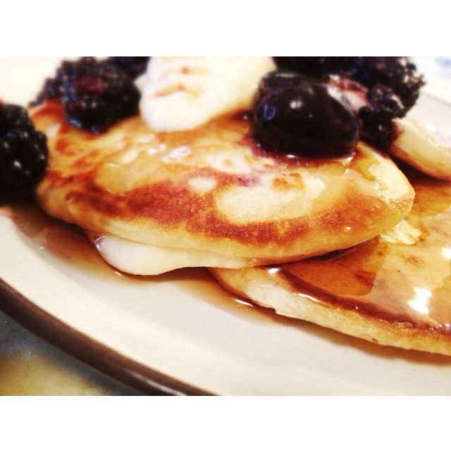 Home made Pancakes for National Pancake Day with warm berries and syrup.