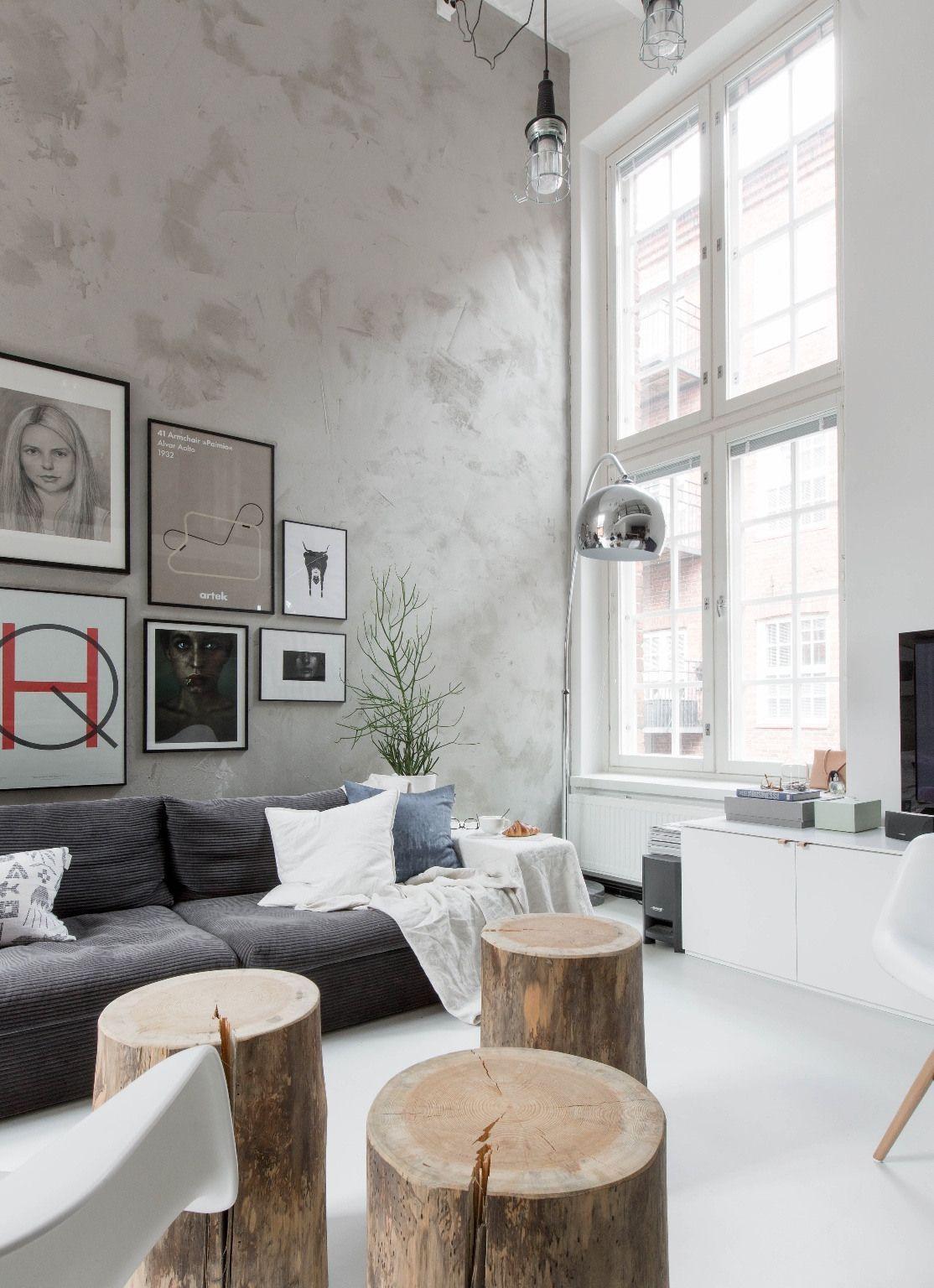 Sala com parede de concreto e pé direito alto